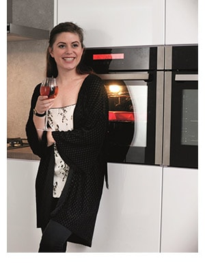 Mum relaxed with a glass of wine next a self cleaning oven and smiling