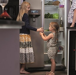 Oldest daughter helping youngest daughter with ice and water dispenser on pc71