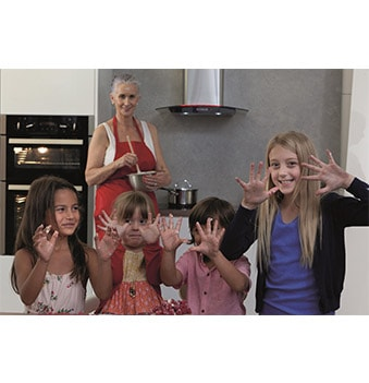 kids showing off their hands after baking with grandma
